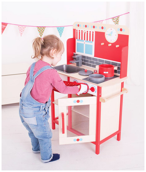 Girl playing with her Bigjigs Play Kitchen